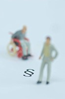 Minature figurines in wheelchair and businessman figurine on white background