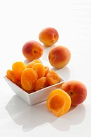 Fresh and dried apricots on white background, close up