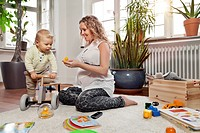 Germany, Bonn, Pregnant mother playing with son in living room, smiling
