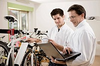 Germany, Bavaria, Mechanics testing electric bicycle with laptop