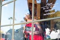 Waitress putting open sign in window