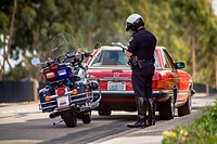 A motorcycle policeman writes a ticket at a traffic stop in Orange, CA