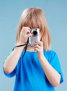 boy with long blond hair taking pictures with digital camera - isolated on blue