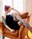 A tattooed 24 year old red headed woman wearing a small black dress indoors