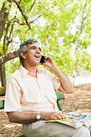 Man talking on a mobile phone and smiling, Lodi Gardens, New Delhi, India