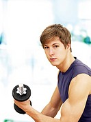 Young man doing strength training with a dumbbell, muscular