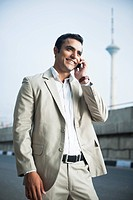 Businessman talking on a mobile phone at roadside
