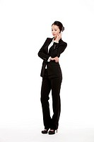 A young businesswoman posing in a studio with a mobile phone.