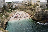 Italy, Puglia, lined by sheer cliffs; Polignare del Mare, Polignano a Mare beach has golden sand that slips into bright clear green water