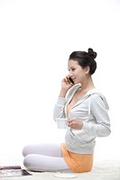 A young woman sitting with a cup of coffee and talking on a mobile phone.
