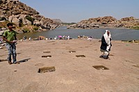People On The Ancient Ghats On The Tungabhadra River In Hampi With Hanuman Temple In Background