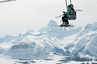 Skiers On Ski Lift With Mt. Assiniboine At Sunshine Village Ski Resort In The Canadian Rockies