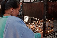 Kathmandu, Nepal. Nepali Lady Lights a Candle at a Shrine adjacent to the Manu Ganesh (Ashok Binayak) Shrine, Durbar Square