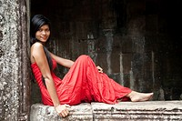 Beautiful Cambodian woman wearing a red dress posing at Bayon temple in Angkor Thom Cambodia.
