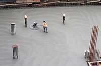 Canada, BC, Vancouver. Construction worker leveling concrete on floor our new building.