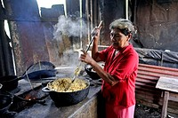 Woman, 58, preparing tortillas in a simple wood stove in a kitchen *** No publication in Nicaragua ***