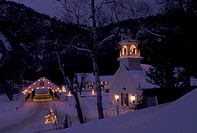 NH, New Hampshire, Stark, Christmas lights decorate the Stark Union Church and covered bridge in the evening in winter.