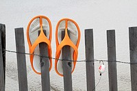 Flip Flops and fishing lure hanging on a beach dune fence. Lavalette, New Jersey, USA.