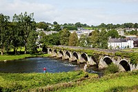 A bridge crossing the river nore with a man fishing at the water's edge;Inistioge county kilkenny ireland