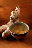 Cup of ginger tea and fresh ginger.