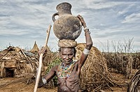 Old Dassanech woman carrying a big pot over her head near Omo river, Omorate, Ethiopia.