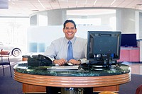 Car salesman at desk in car dealership