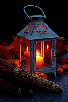 Lantern with candle and autumn crop in the evening.