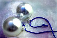 Two silver Christmas baubles on blue ribbon.
