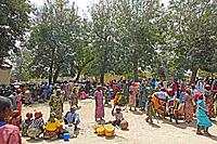 Market scene, women wearing typical calabash helmets and colourful dresses