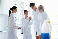Chemistry students looking at test tube in laboratory