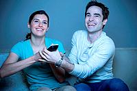 Couple watching television, fighting over remote control
