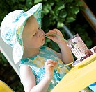 little girl eating a cake and drinking a juice. - 15/07/2008