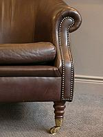 The armrest of an old leather chair with brass studs