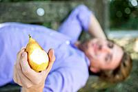 Germany, Bavaria, Munich, Mid adult man lying on bench and eating pear