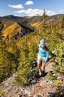 Mixed race woman hiking on rocky hillside