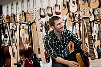 Man choosing electric guitar in guitar shop