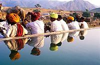 Colourful turbans reflected in a water tank , Pushkar Camel Fair , Rajasthan , India.