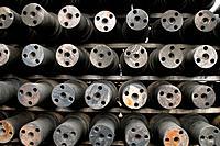 Axles for railroad train wheels stored at machine shop awaiting assembly, Tacoma, Washington USA.