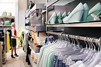 Woman, buyer in fashion shop aisle. Retail outlet with row of hangers, clothes. Fashion store interior.