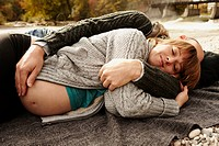 Pregnant woman and partner lying beside river
