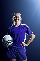 Studio shot of female soccer player with ball
