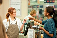 Female shop assistant handing bill to customer