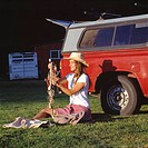 Caucasian Cowgirl Sitting In Front Of A Red Pickup Truck And Holding A Decorated Stick