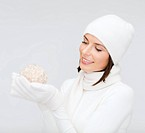 winter, people, happiness concept - woman in hat, muffler and gloves with christmas ball
