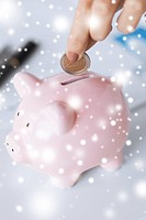 picture of woman hand putting coin into small piggy bank