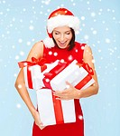 christmas, x-mas, winter, happiness concept - surprised woman in santa helper hat with many gift boxes