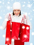 retail and sale concept - happy woman in winter clothes looking into shopping bags