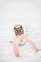 Girl wearing cat mask lying on bed