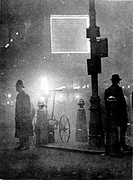 Photograph showing a Policeman (left) standing at a street refuge in Piccadilly Circus, London, during a heavy fog in December 1924. This image was ta...