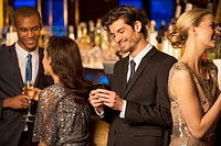 Well dressed man looking down at cell phone and smiling in luxury bar